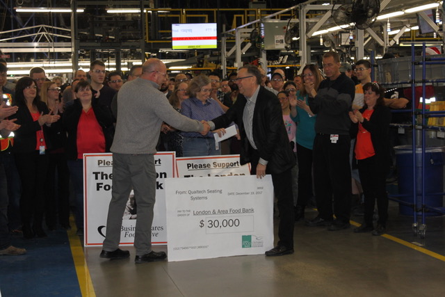 Wayne Dunn receiving a cheque and a handshake at a presentation of Qualtech Seating Systems/Magna Seating and Aslon Management's combined $32.5K donation.