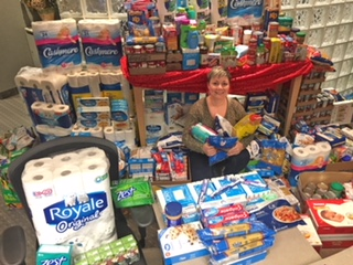A picture of a Davis Martindale employee surrounded by donations for the Food Bank